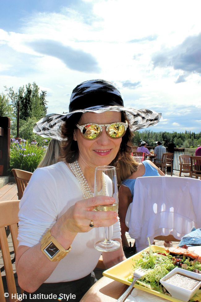 mature woman drinking champagne and eating on a deck wearing a hat and pearls
