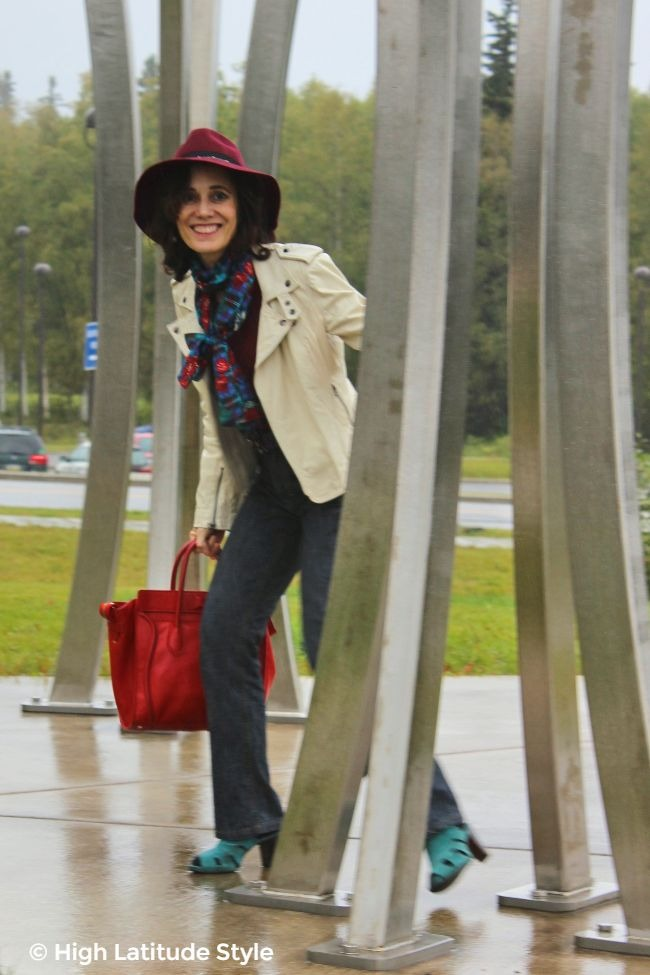 #styleover50 woman in fashion week inspired fall style with biker jacket, scarf, hat, jeans and sandals