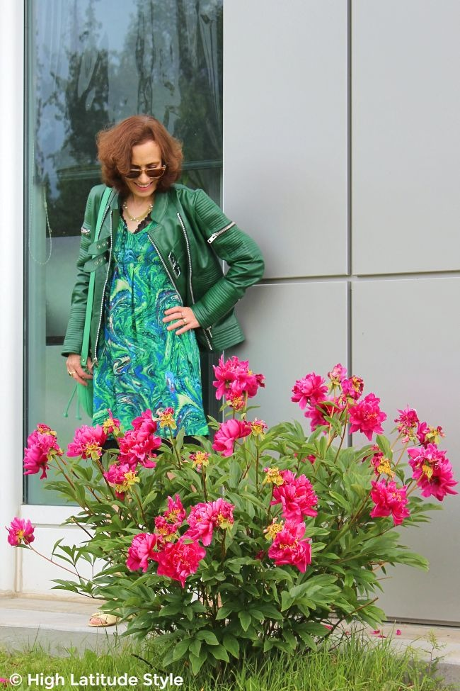 #fashionover50 mature woman in green dress, leather jacket, and bag