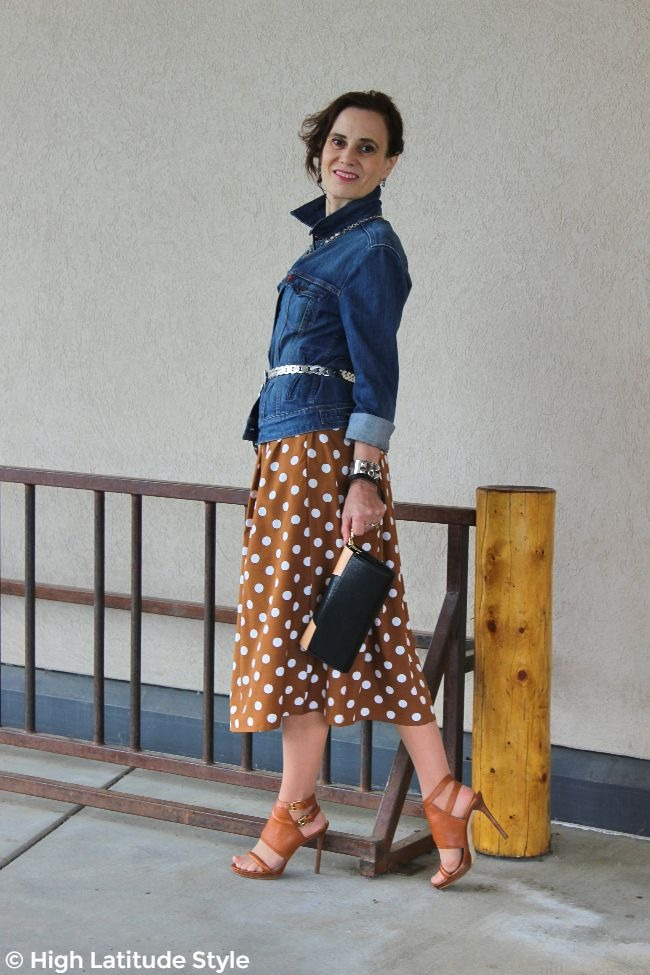 #midlifefashion woman in transitional season work outfit with polka dot dress and denim oversize jacket