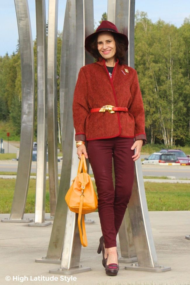 fashion blogger over 50 with a Tenthstreet fedora, burgundy jeans and jacket plus yellow pilage