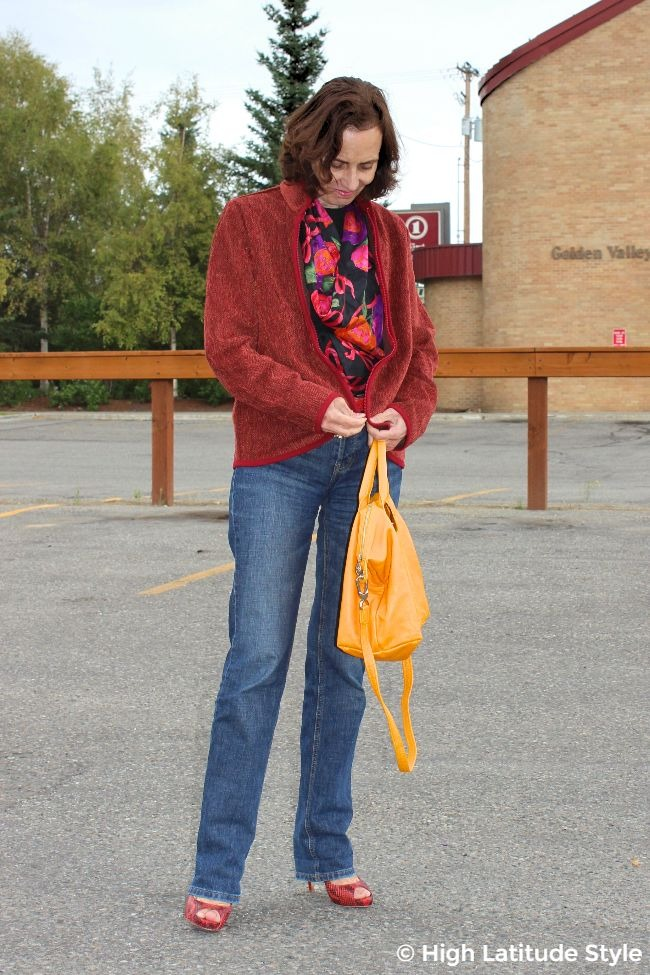 #styleover50 older woman zipping a #WHistleRiver coat worn with BF jeans, scarf, pumps and slouchy bag