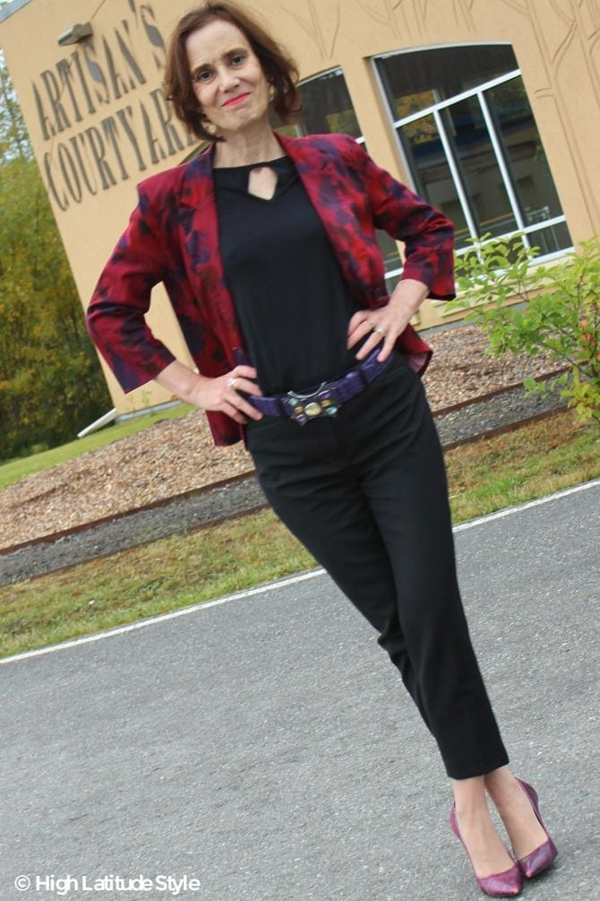 #fashionover50 Blogger Nicole in black key-whole top, cropped pants, abstract floral print blazer with purple pumps and belt