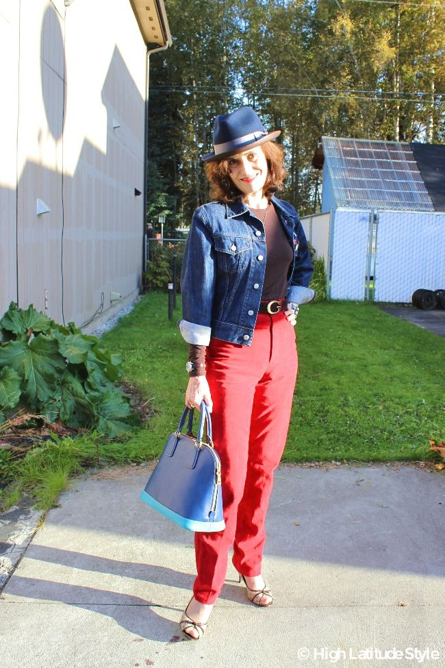 #maturestyle woman in red suede pants, denim jacket, brown T-shirt, and blue brown head gear