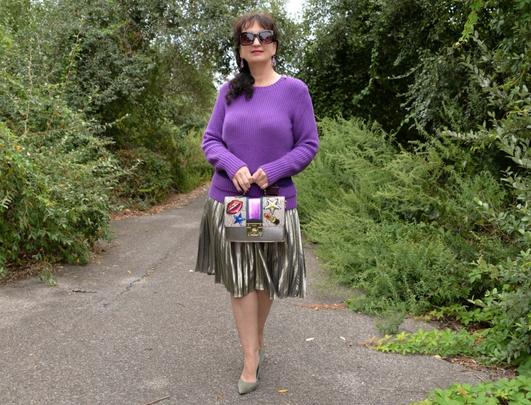 Krystyna in a classic pleated skirt and sweater with pumps and a statement bag.
