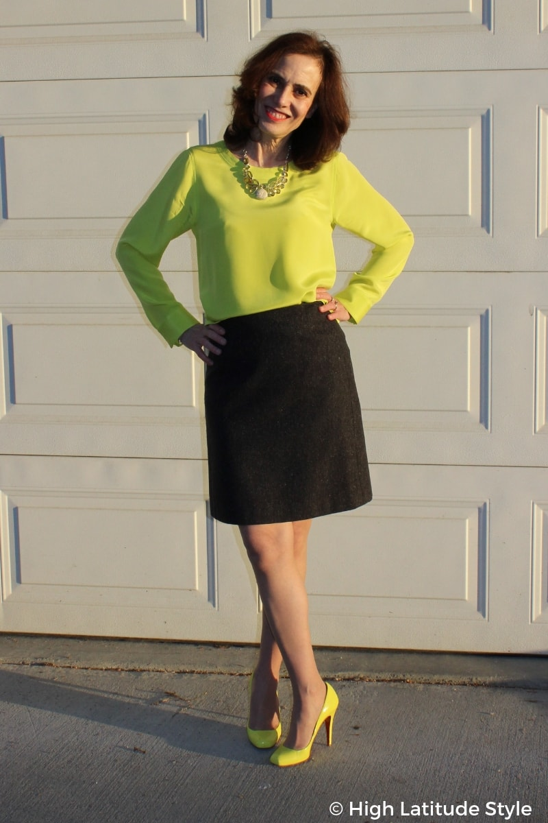 over 50 years old style blogger Nicole in gray above the knee skirt, neon yellow top and heels with yellow statement necklace