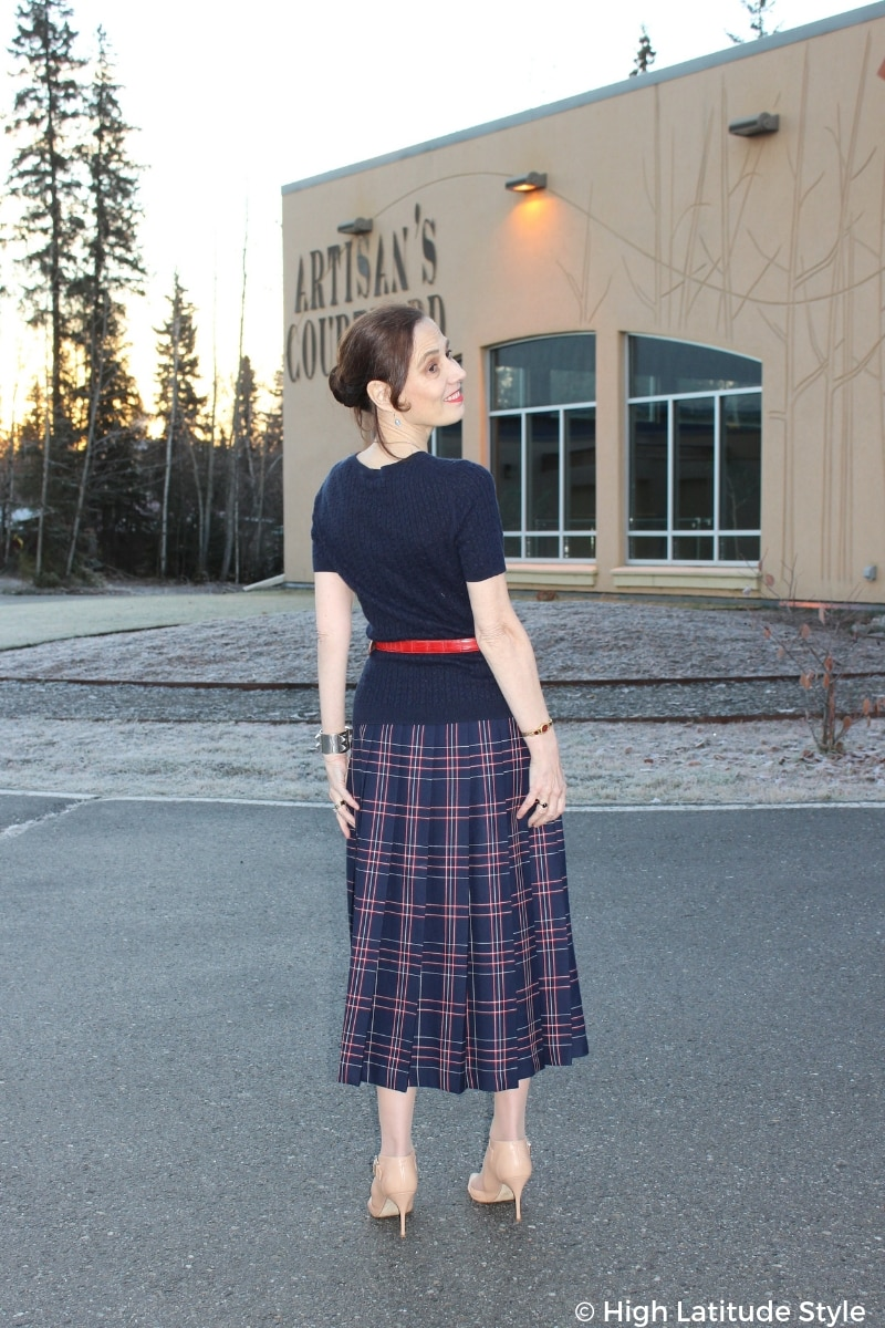 over 50 years old stylist in pleated plaid wool skirt, cable knit top, belt and nude pumps in autumn