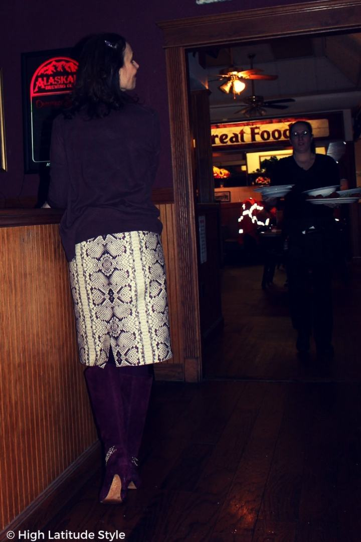 #fashionover50 mature lady in a burgundy, gray, brown and winter white office look with twinkle lights in the background