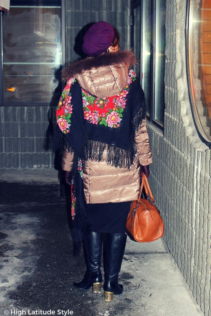 fashionista looking cozy in a downcoat styled with Russian scarf, knit midiskirt, statement boots and beret