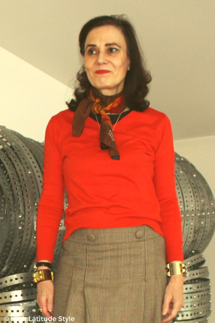 over 50 years old fashion blogger in top layered under bold color sweater, pleated glen check skirt with matching silk scarf