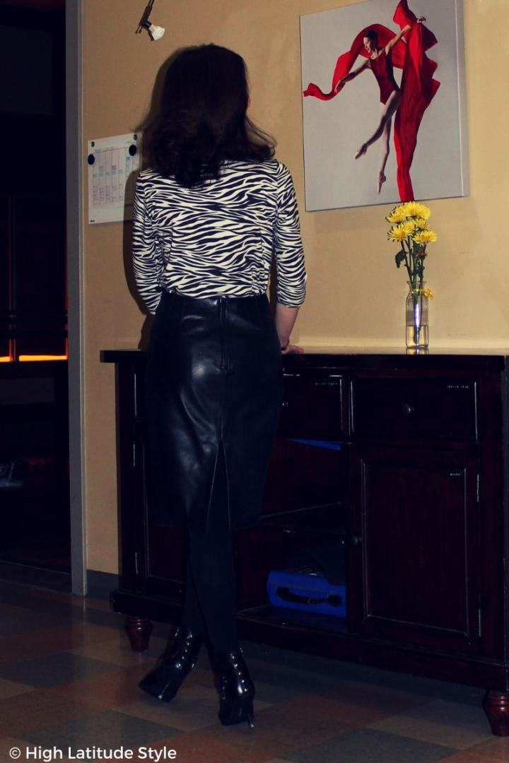 #midlifestyle mature woman in black and white outfit with leather skirt and animal print sweater