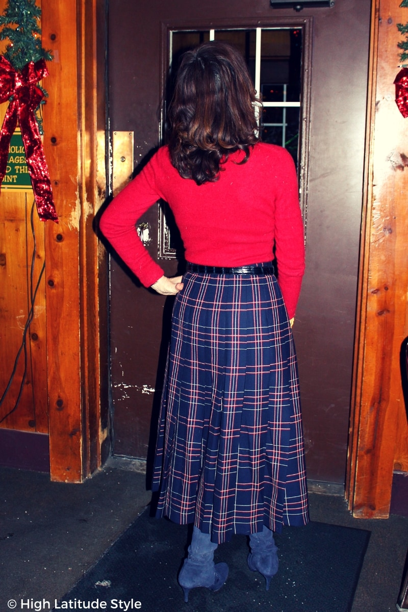#styleover50 woman in midi skirt with pullover in front of a door