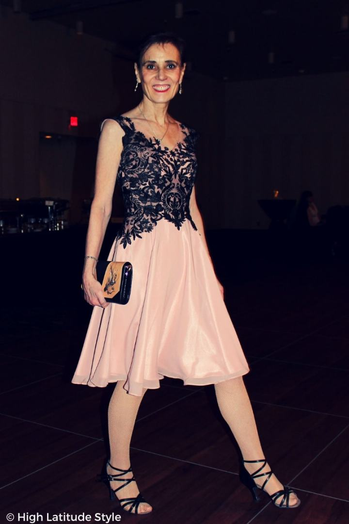 #advancedstyle Nicole walking in strappy sandals in a lace chiffon gown carrying a fish pearl embellished wrist bag