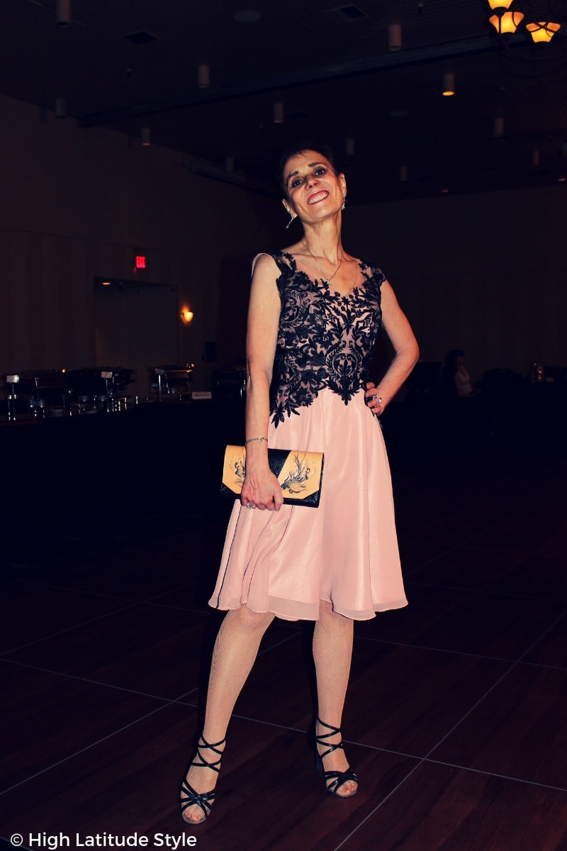 over 50 years old fashion blogger posing on the dance floor in front of the buffet in evening dress and matching sandals
