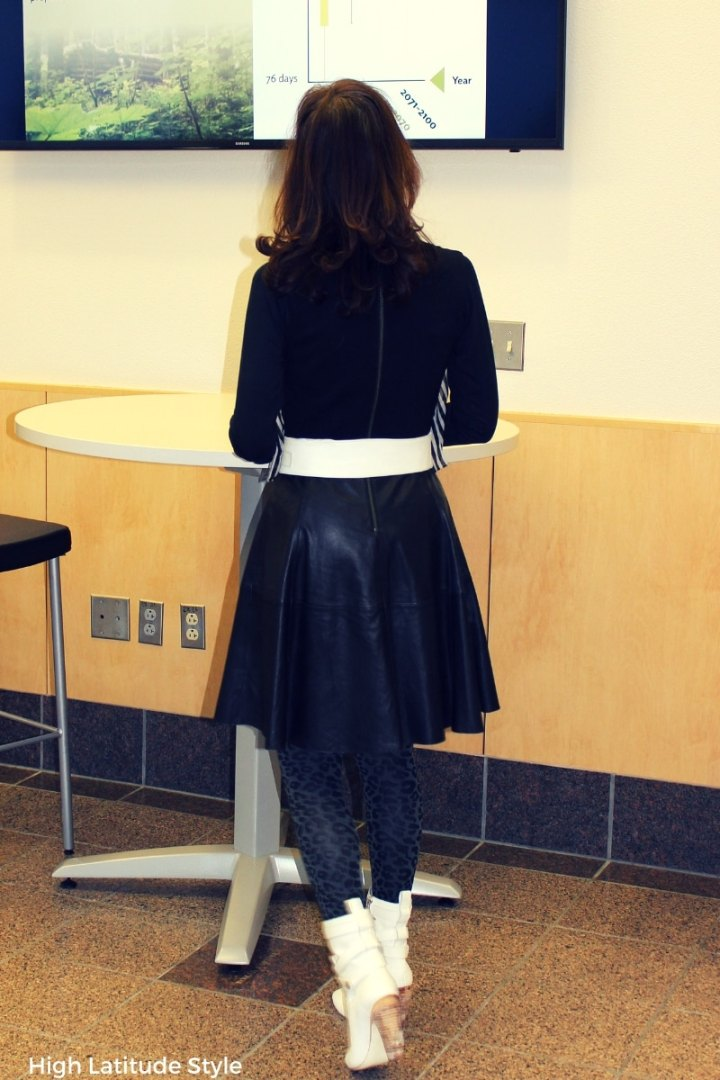 older woman in fit-and-flare attire with leather skirt and white booties