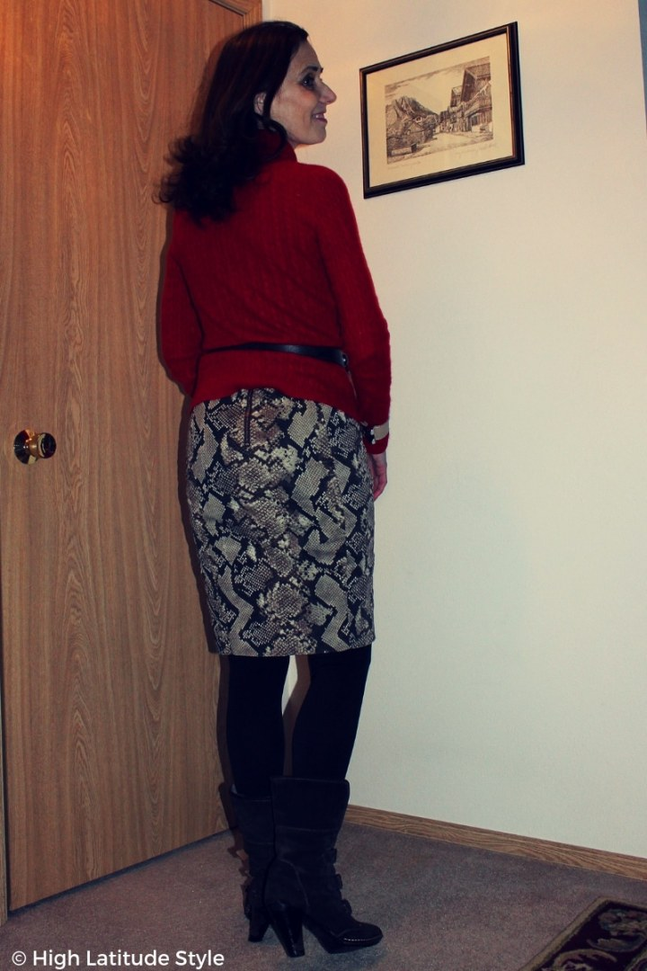 Nicole wearing a snakeskin skirt with red top, tights, belt and boots