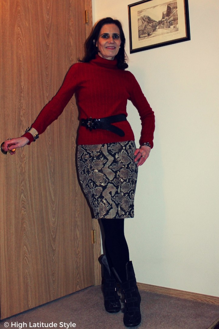 over 50 years old woman in business casual office look with snake print skirt styled with sweater, tights and boots