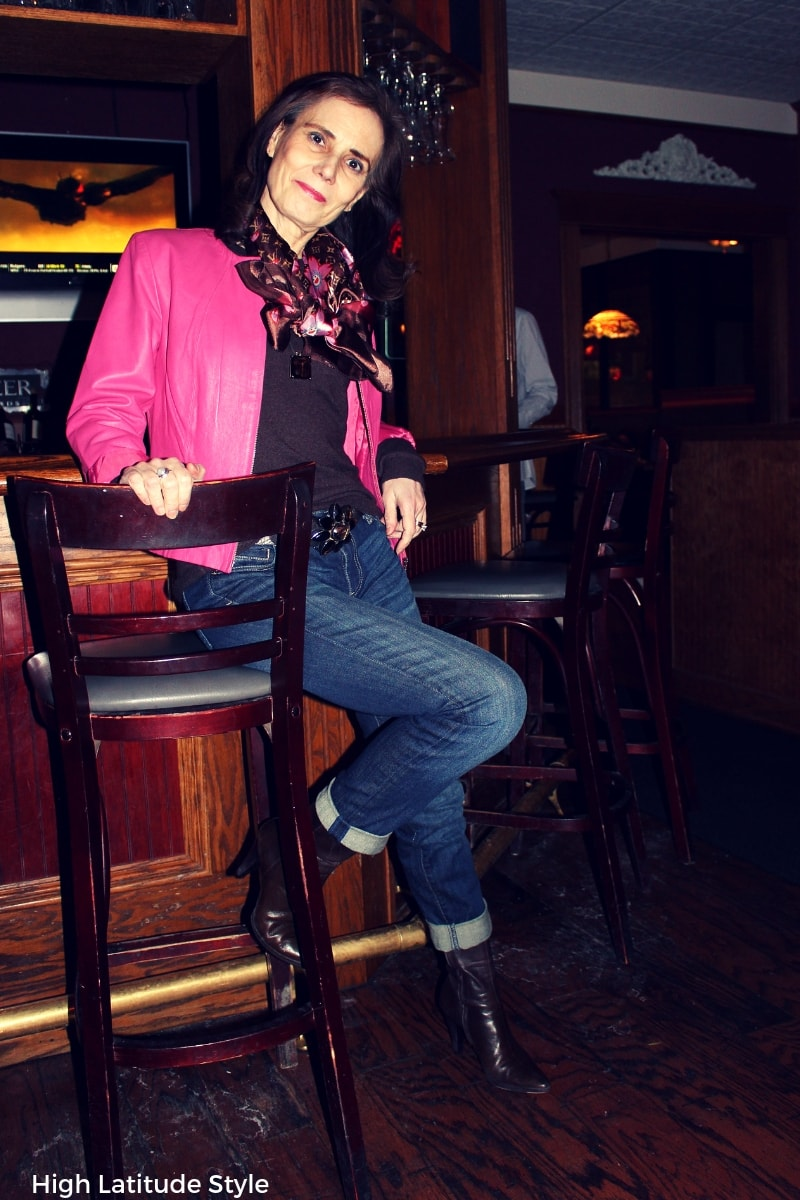 #fashionover50 fashion blogger sitting in boyfriend jeans, pink jacket, brown sweater and scarf