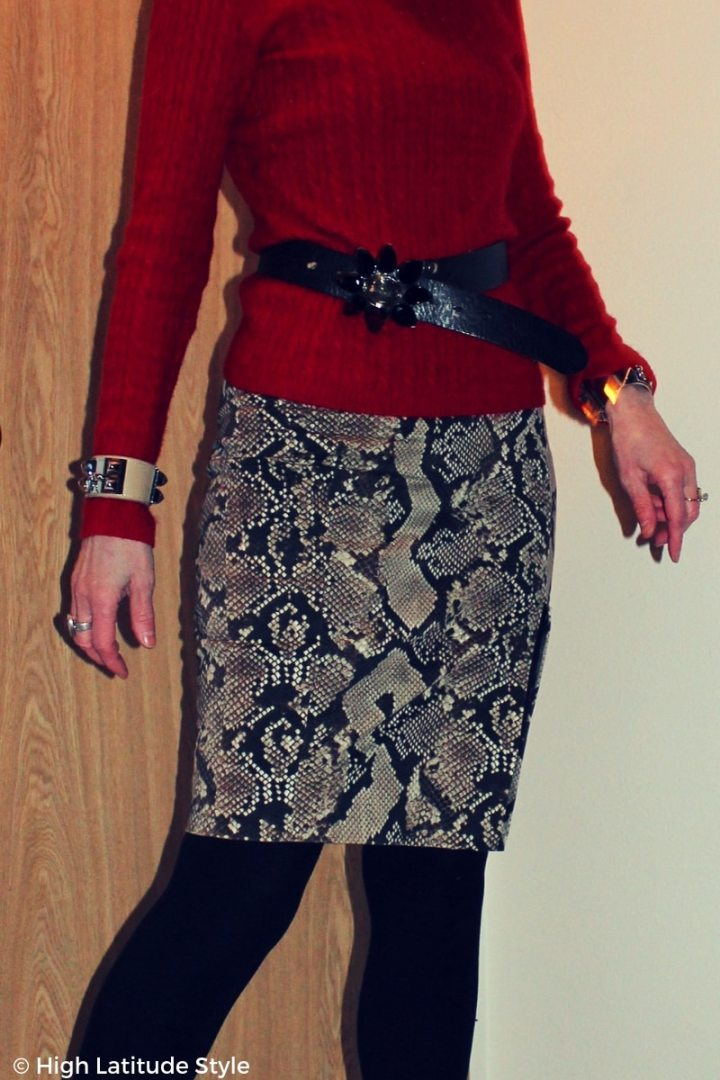 Details of snake print, sweater, and belt buckle