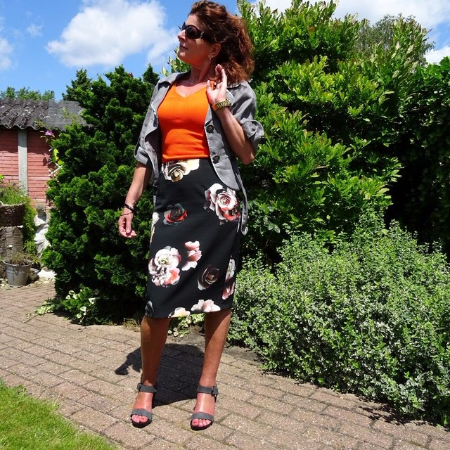Nancy Baten in orange top, cropped jacket and floral skirt