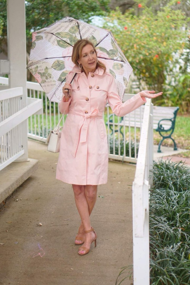 Nina Bandoni in a baby pink trench coat, sandals and a floral umbrella