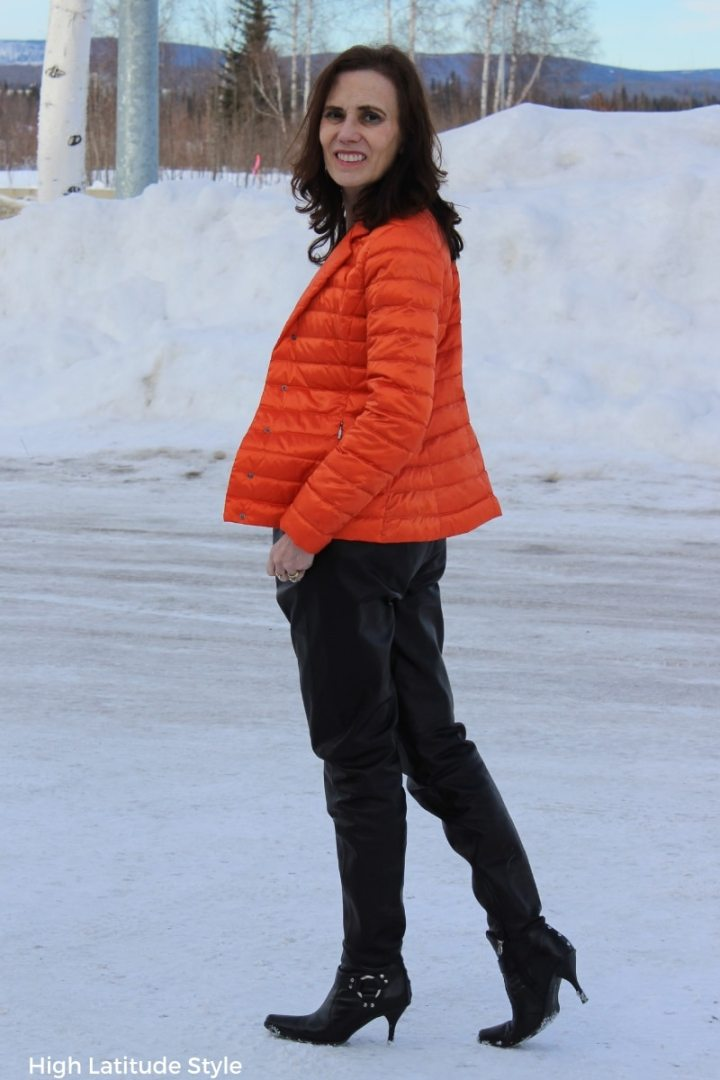 Nicole in black leather jogging pants and orange jacket