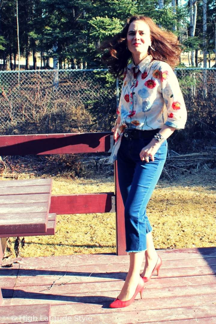 midlife blogger in floral print top, red pumps and denim trousers