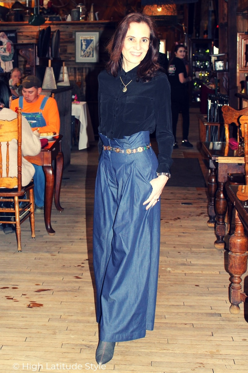 Nicole of High Latitude Style in trendy trousers, gemstone belt, pendant necklace, and silk blouse