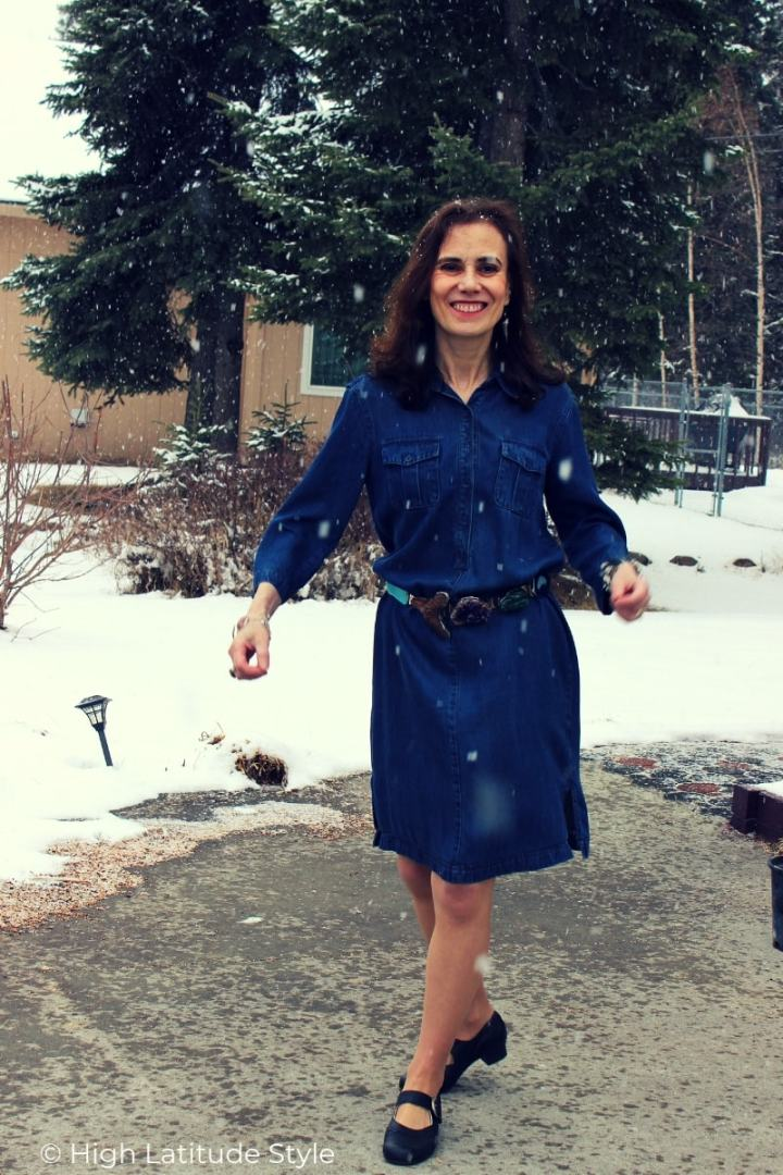 over 50 years old fashion blogger in jeans tunic with gemstone belt and ballerina shoes in a yard