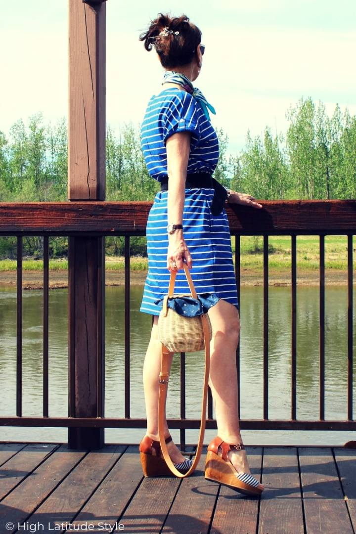 mature woman standing on a deck at a river in shorts blue and white dress and sandals