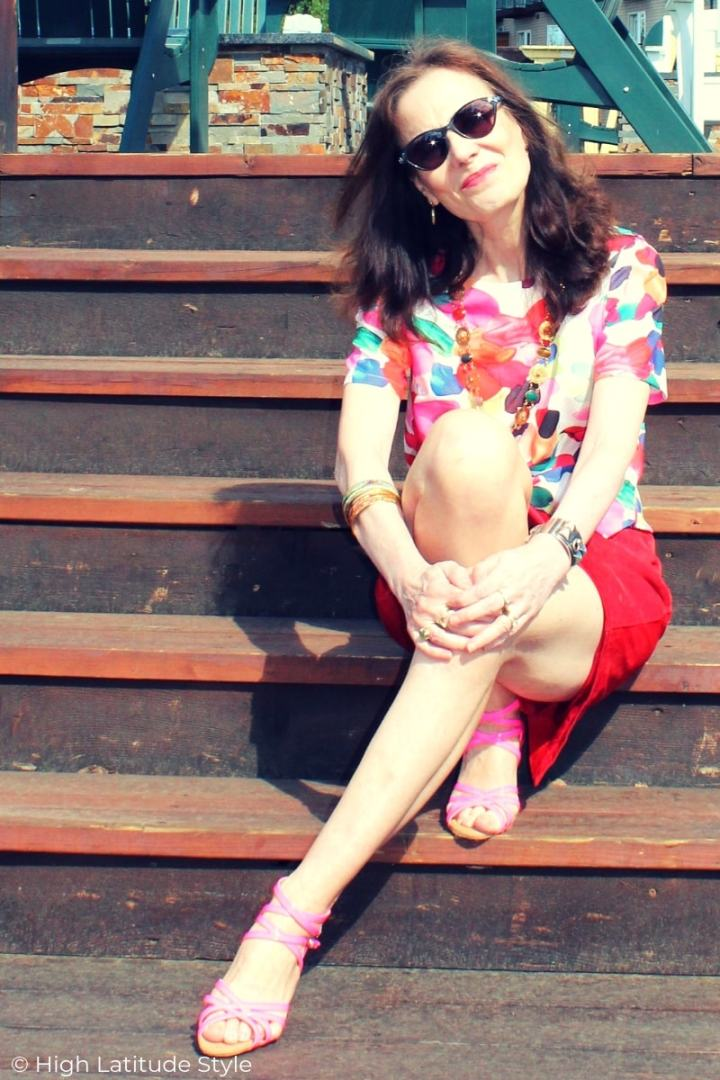 mature woman in printed cropped top, red skirt, pink strappy sandals and cateye sunglasses