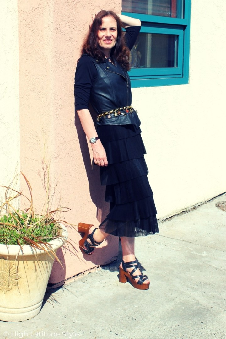 over 50 years old fashion blogger in all black street chic with skirt, leather vest, charm belt, top and wood clog sandals