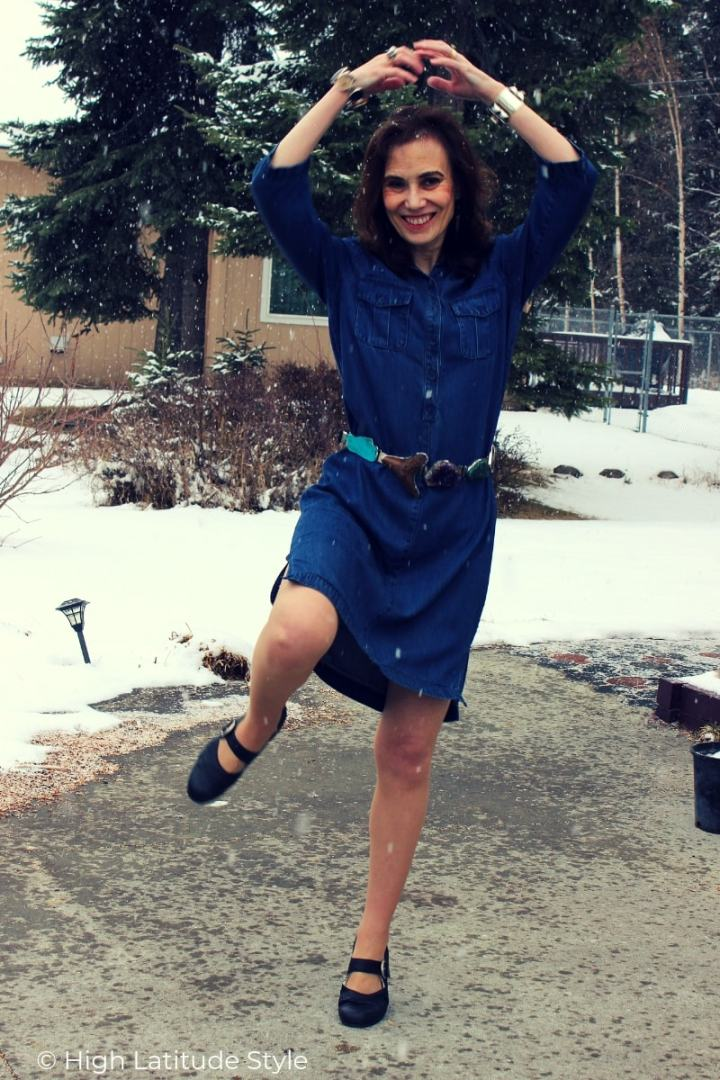 over 50 years old Alaskan blogger dancing in the snow in work outfit with ballet flats