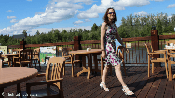 Alaskan midlife woman in sleeveless designer summer dress walking at the river