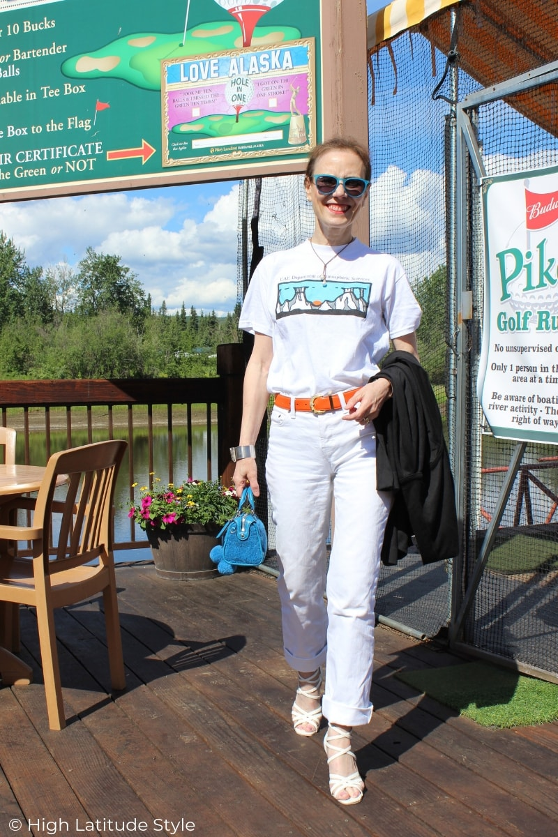 Alaskan woman in all white casual summer look of pants, T-shirt and sandals with pops of color