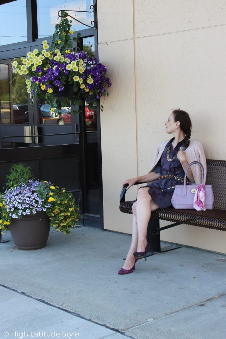 Nicole of High Latitude Style sitting on a bench in a summer business casual with dress, jacket and pumps