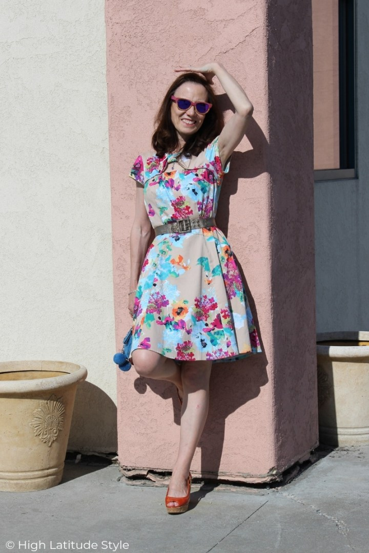 over 50 years old fashion blogger in floral print cotton dress, wood frame sunglasses, cork plateau heels