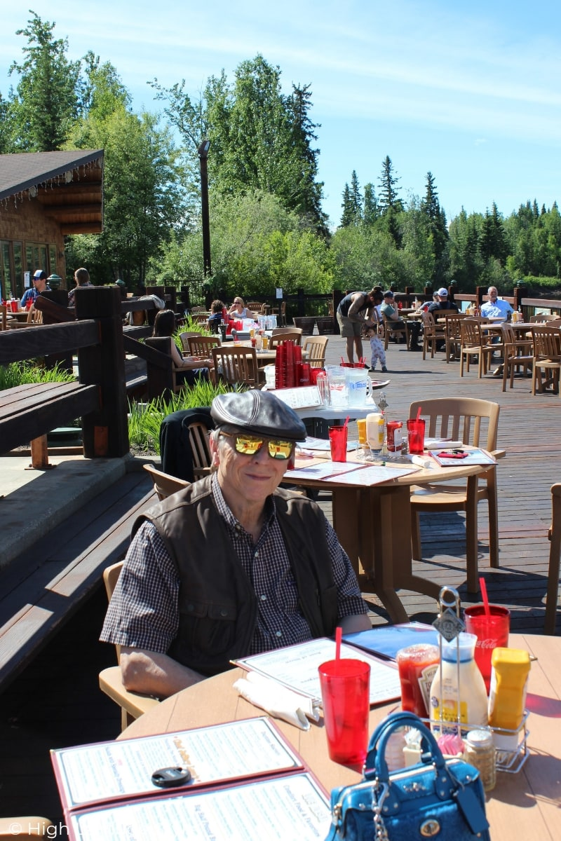 man sitting at a table on a deck in Alaska in June
