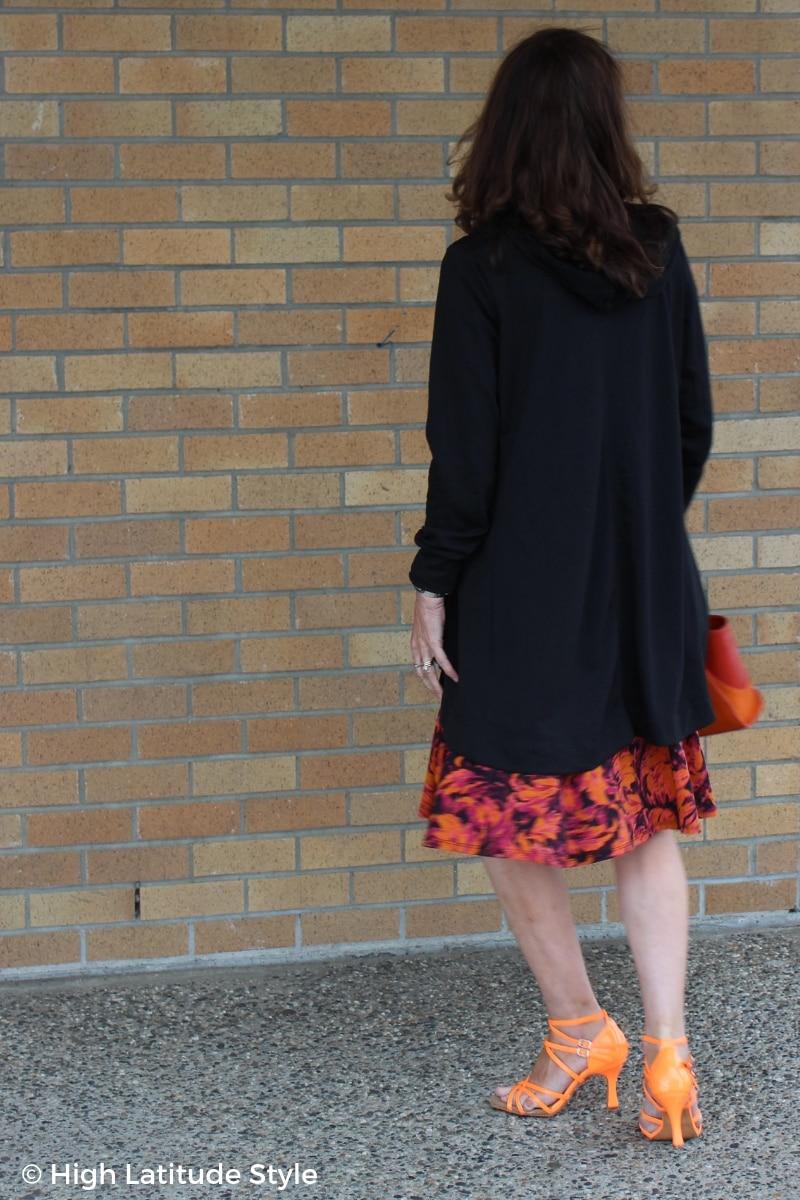 mature woman a long black hoodie over a dress