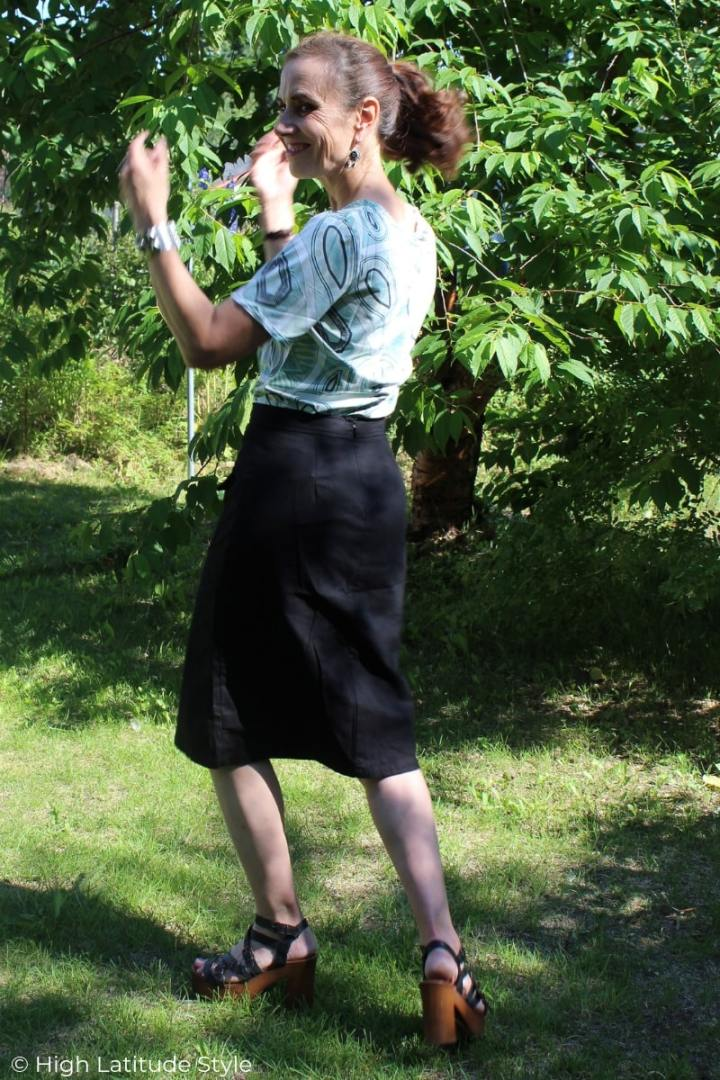 style book author frolicking ins a California Casual skirt, wood sandals and T-shirt look