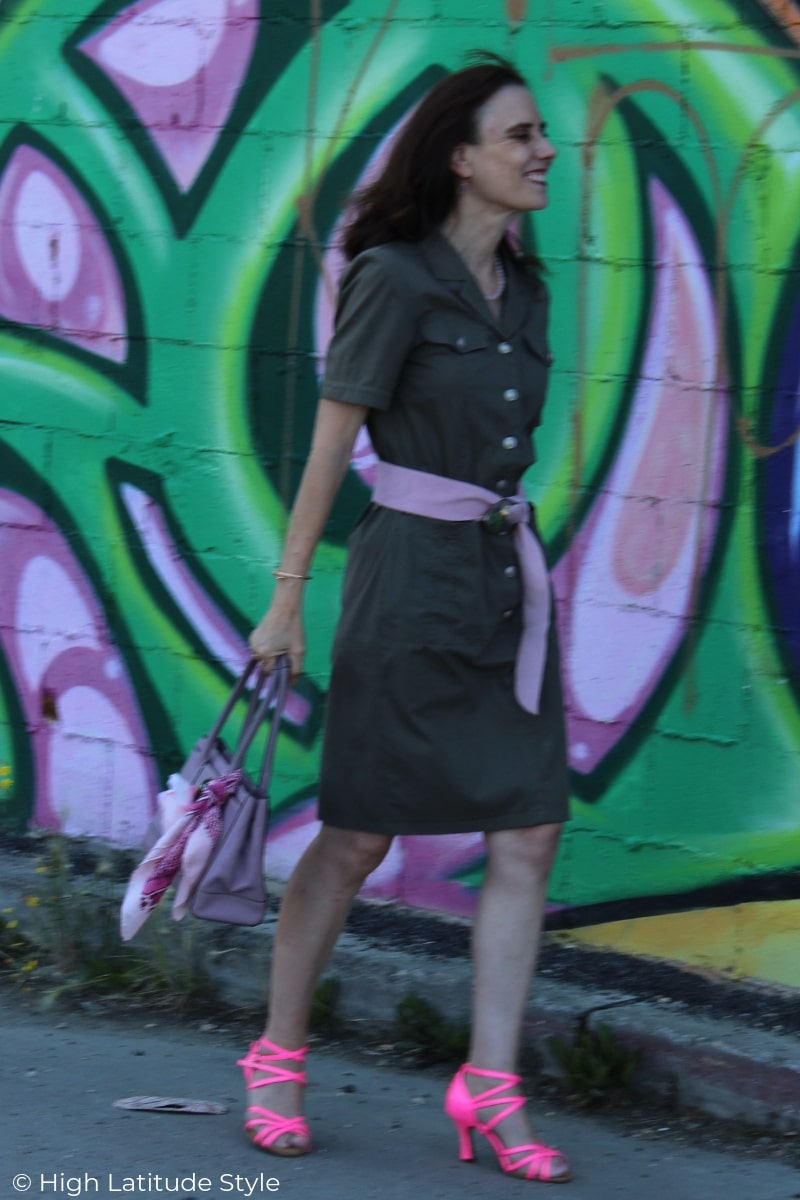 blogger Nicole of High Latitude style donning street wear in magenta, pink, and olive military inspired dress in front of a mural