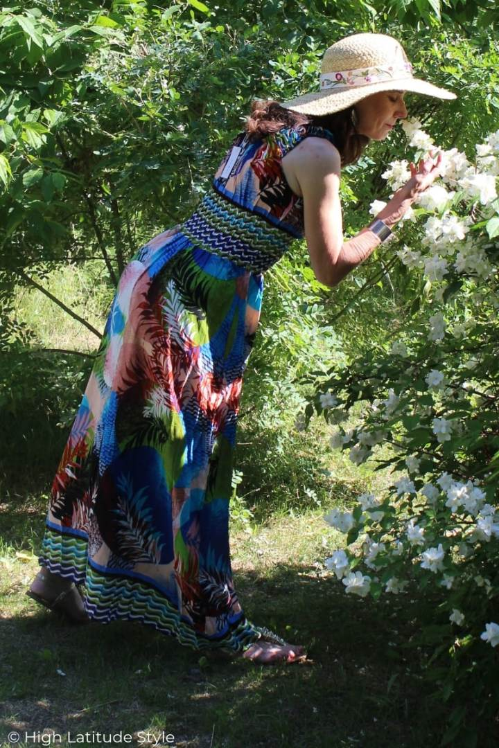 woman in colorful long sleeveless dress and wide brim hat smelling the flowers