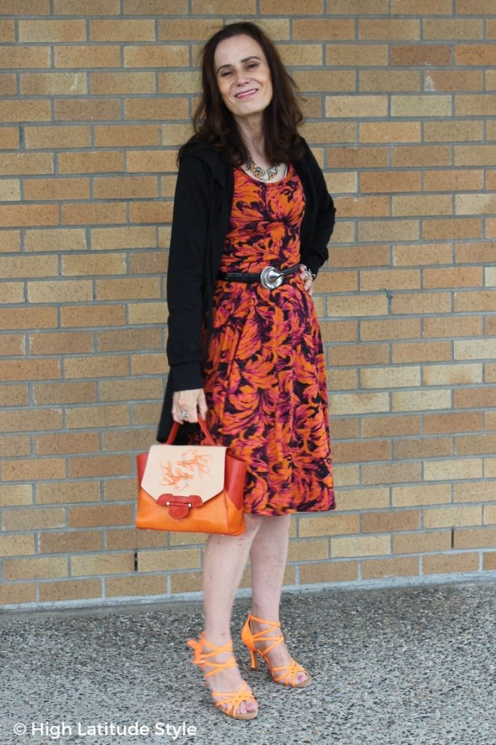 Nicole of High Latitude Style in orange purple and black dress with orange bag and sandals