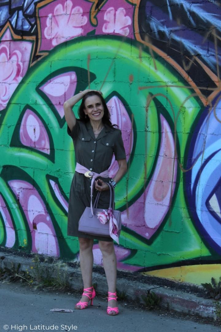 fashion blogger in olive shirt dress, pink belt and sandals, lilac bag