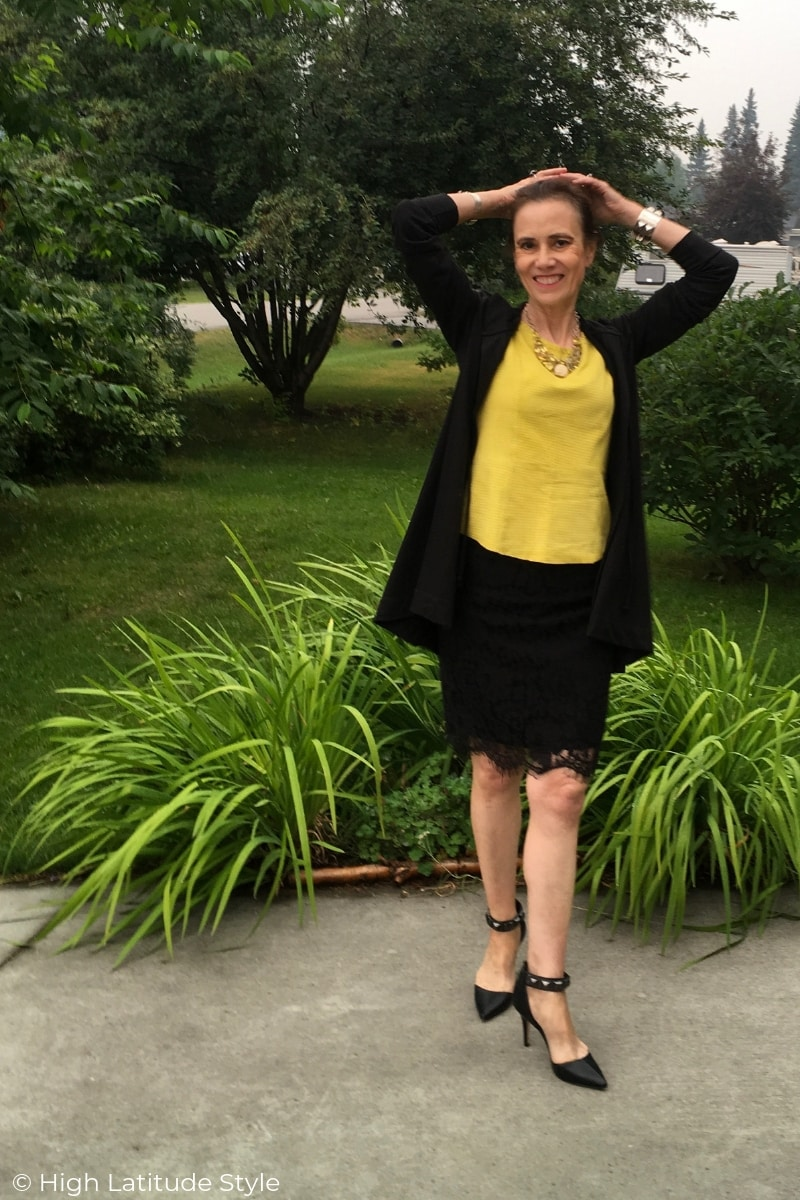 style blogger in neon conseigned yellow top witgh black skirt and designer cape