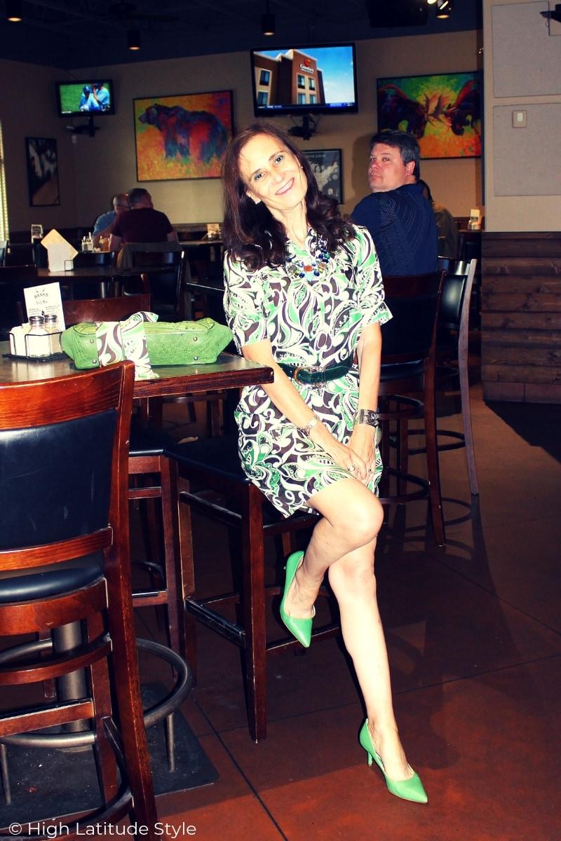 Nicole sitting on a bar stool in a shirt dress