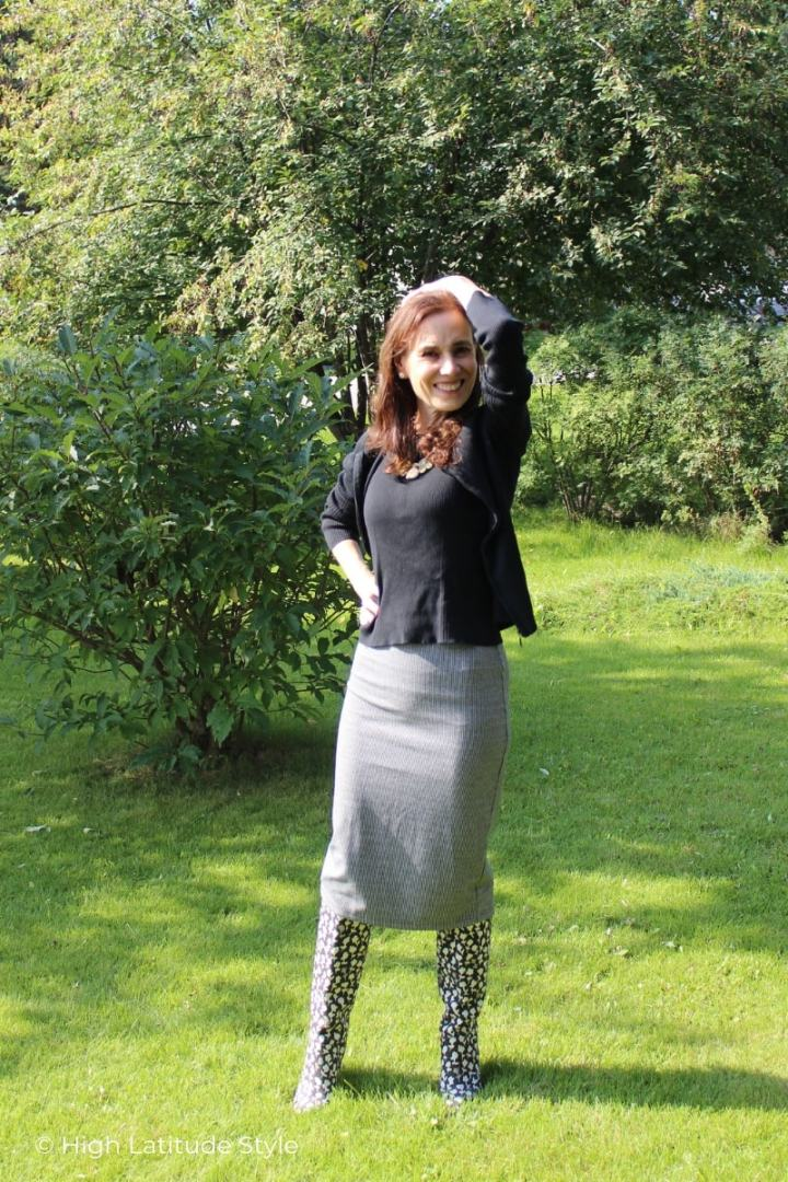 midlife woman in black and white pencil skirt, boots and twinset