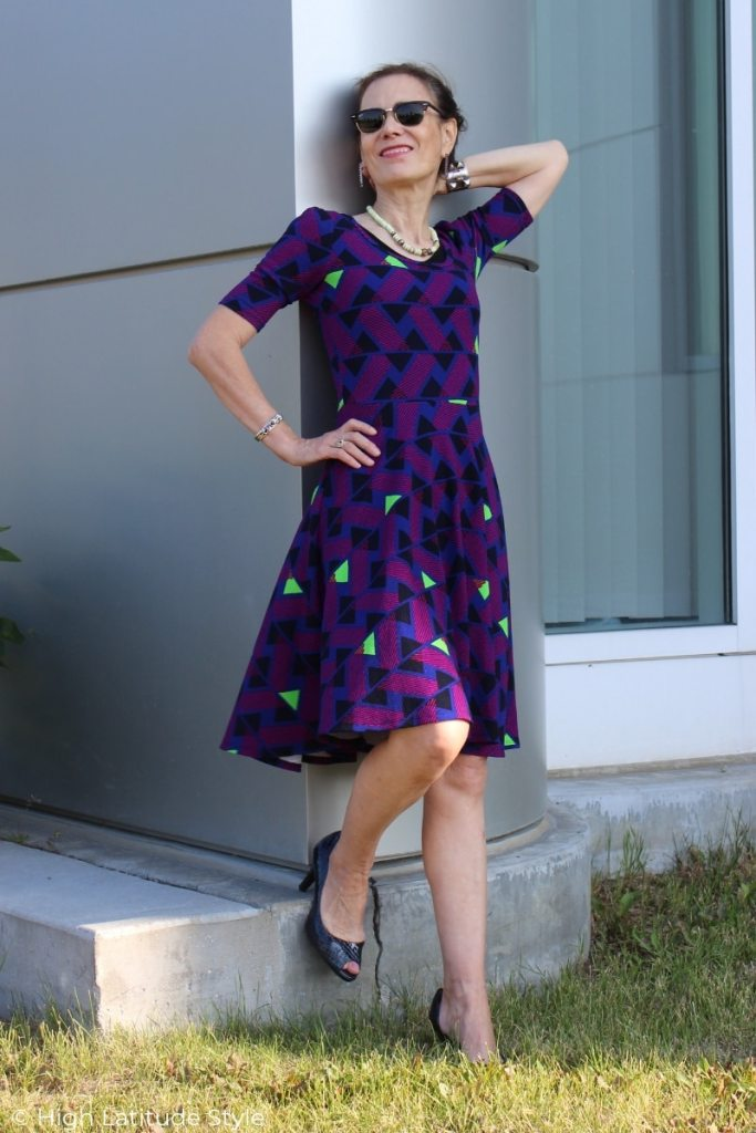Nicole of High Latitude Style in purple, red, blue black and neon yellow fit-and-flare dress
