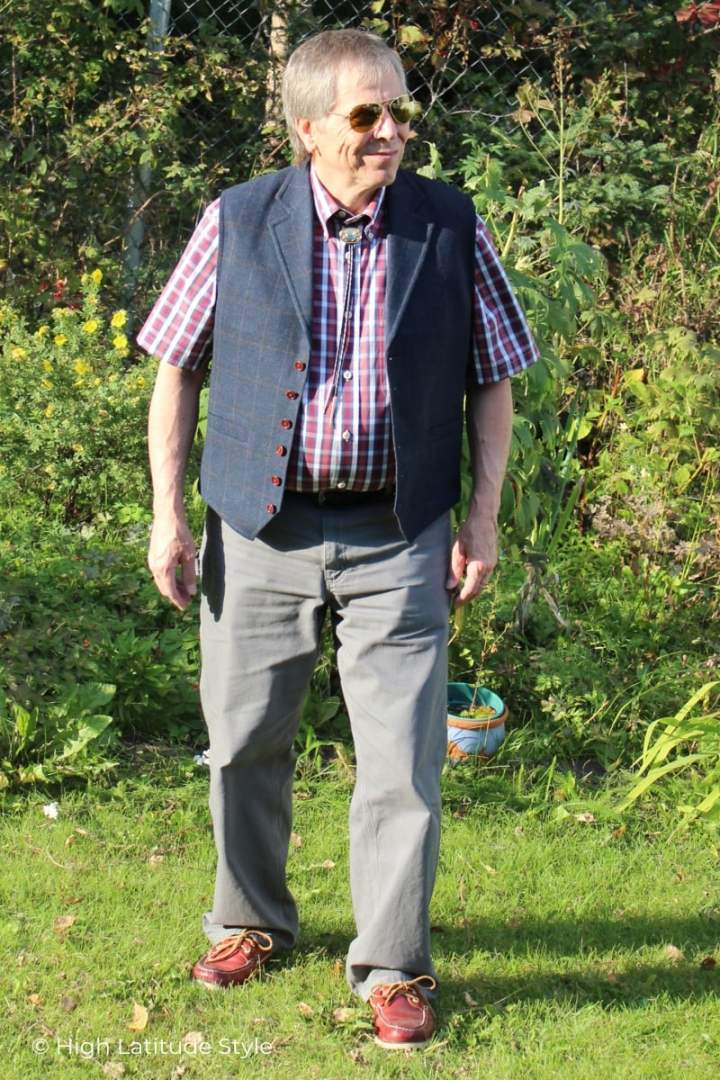 man in casual fall outfit with plaid shirt abd vest, trousers and mocasins