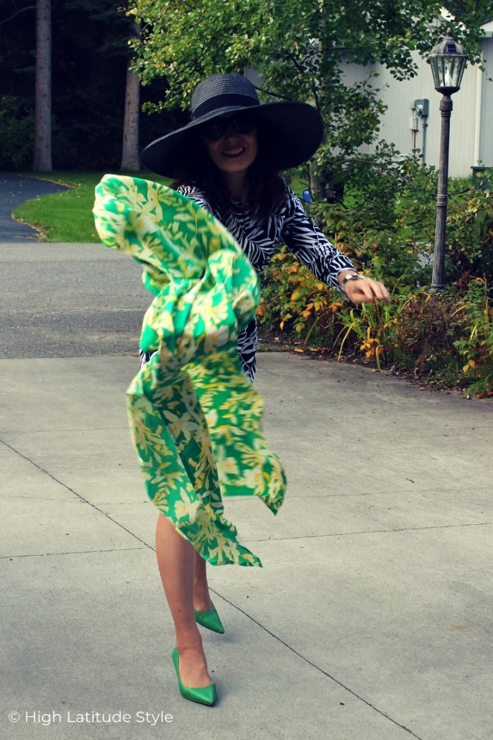 woman over 50 in a weekend dress, hat and pumps throwing a scarf
